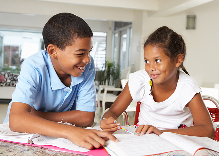 Two students work together on an assignment. She grins when he points to a certain place on the assignment sheet.
