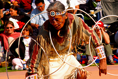 Man performs Native American Pow-wow dance for audience.
