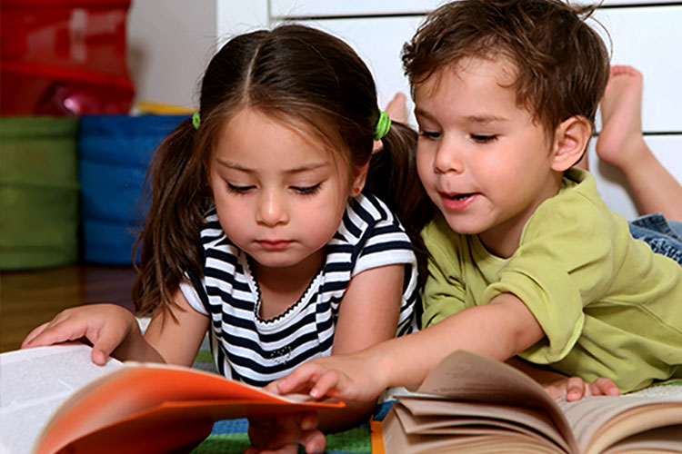 Pre-school children help each other learn to read.
