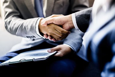 "two people shake hands to ""Seal the deal"" on a business transaction."